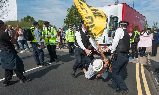 Police move a protester from the road as a truck tries to make a delivery to the DSEI arms fair in London. Photograph: Peter Marshall/Demotix/Corbis