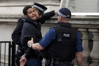 A demonstrator protesting against Bahrain's King Hamad bin Isa al-Khalifa's visit to Britain is handcuffed by police officers, near Downing Street in London October 26, 2016.   REUTERS/Peter Nicholls
