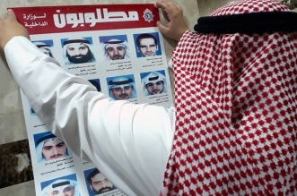 "An official from Kuwait's interior ministry puts up a poster on July 20, 2017 in a Citizen Service Centre in Kuwait City, of fugitives convicted of belonging to a cell that had been formed and trained by Iran's Revolutionary Guards who were accused of plotting attacks in the state. Kuwait expelled Iranian diplomats and closed some embassy missions after the emirate's top court convicted a ""terror"" cell of links to the Islamic republic, prompting Iran to threaten reciprocal measures. / AFP PHOTO / Yasser Al-Zayyat"
