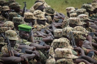 Soldiers of the Uganda People's Defence Force (UPDF) attend a special event before starting their service under the auspices of the African Union Mission in Somalia (AMISOM) at the Singo military camp, 75km north of Kampala on April 12, 2018. After completing 6 months training, 1822 soldiers will serve peacekeeping mission for a year at their base in Arabisca, 31 km outside of Mogadishu, Somalia.  / AFP PHOTO / Gael Grilhot